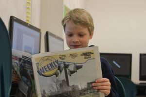 Zach learns the elements of a newspaper with an older issue of the O'Fallon Weekly. (O'Fallon Weekly Photo by Nathan Poignee)