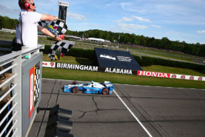 Simon Pagenaud screams past as the checkered flags are waved.  (Photo by INDYCAR Photo – Bret Kelley)