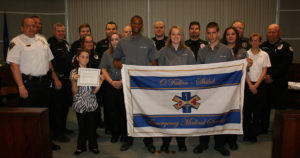 The O'Fallon EMS and their new Explorer unit proudly display the department's new flag. Mayor Gary Graham proclaimed May 16-20 as O'Fallon EMS Week at Monday's City Council meeting. (Submitted Photo by Pam Funk)