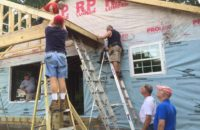 The first sheet of roof sheathing gets nailed on by Gary Mueller, Bob Kueker, and Jeff Greenstreet. Jim Means and Jim Campbell look on. (Submitted Photo)