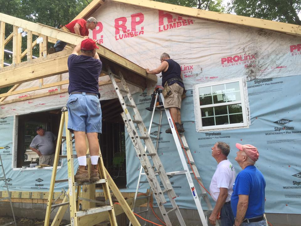 The first sheet of roof sheathing gets nailed on by Gary Mueller, Bob Kueker, and Jeff Greenstreet. Jim Means and. Jim Campbell look on. (Submitted Photo)
