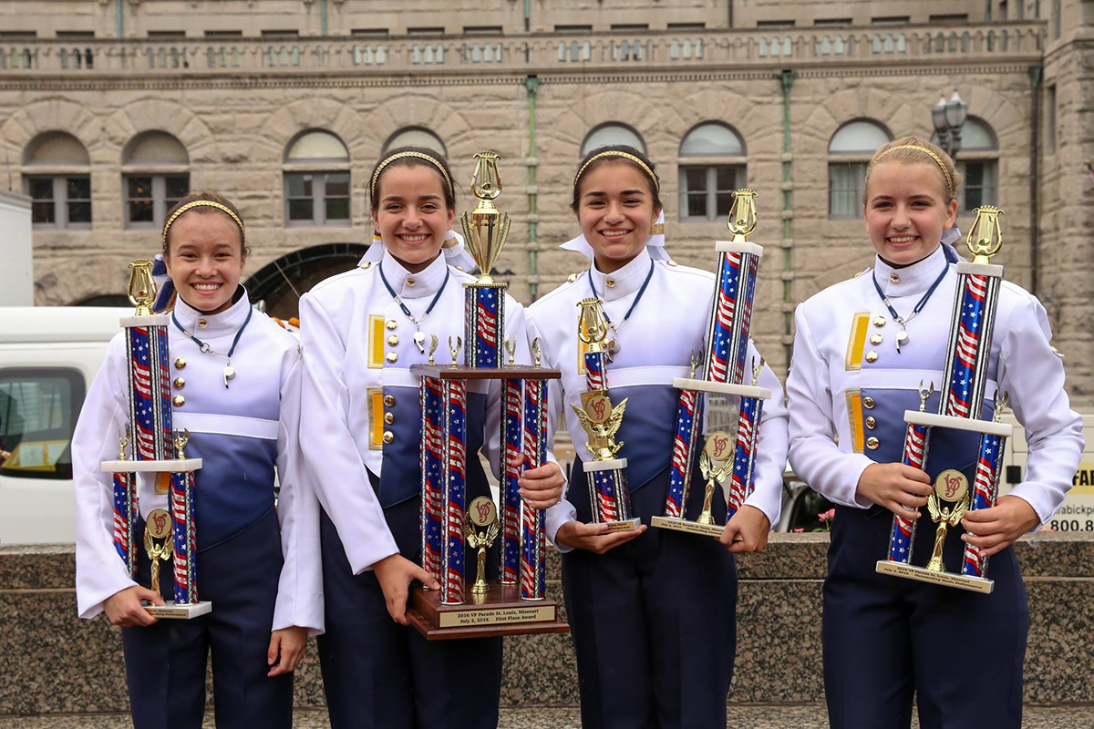 Drum majors Hannah Riseberg, Lilly Schmidt, Bianca Castillo, and Claire Wilcox hold up trophies earned for Participation, Best Marching Performance, Best Music, Best General Effect, and First Place Overall in the Liberty Drum Challenge at the Veiled Prophet Parade in downtown St. Louis. (Photo by Tim Grout)