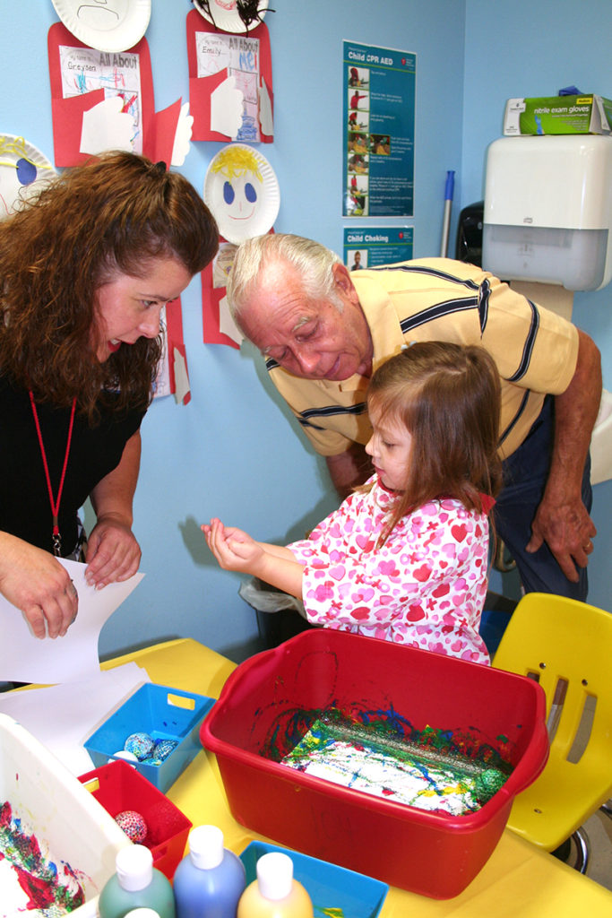 Teacher Bridget Wilson instructs Adalay Mabee and her grandfather on a classroom art project. (Submitted Photo)