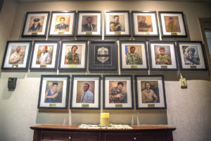 The memory of six fallen heroes killed Dec. 21, 2015 by a suicide bomber near Bagram Air Field, Afghanistan is still strong at the Air Force Office of Special Investigation headquarters at Scott Air Force Base, Ill. The four OSI special agents, Micahel A. Cinco, Chester J. McBride, Peter W. Taub and Adrianna M. Vorderbruggen; and two Security Forces defenders, now honorary special agents, Tech. Sgt. Joseph G. Lemm and Staff Sgt. Louis M. Bonacasa, had their Hall of Heroes portraits added to the wall alongside 10 previous fallen heroes.  (U.S. Air Force photo by Airman Daniel Garcia)