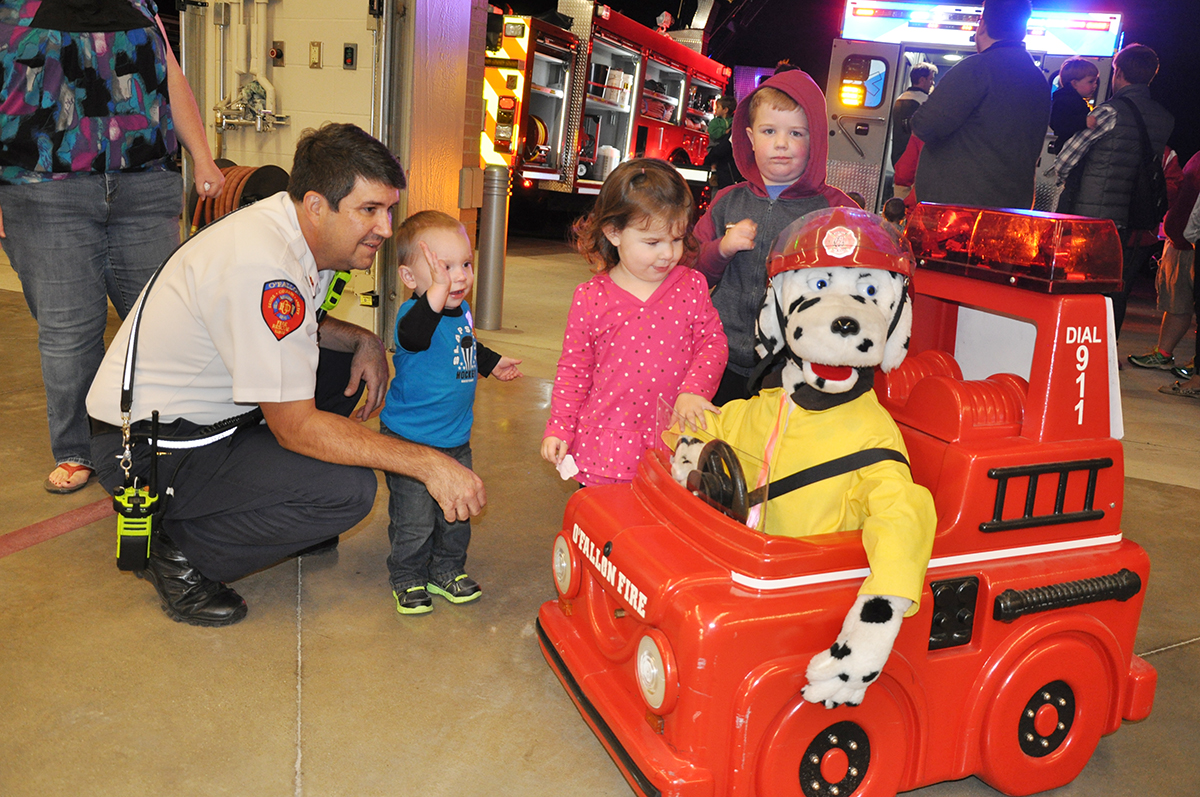 Grayson Fechtler, Lily Martin and Nicholas Martin talk with a member of the O'Fallon Fire Department as they check out Sparky in his shiny red fire truck. (O'Fallon Weekly Photo by Jeff Egbert)