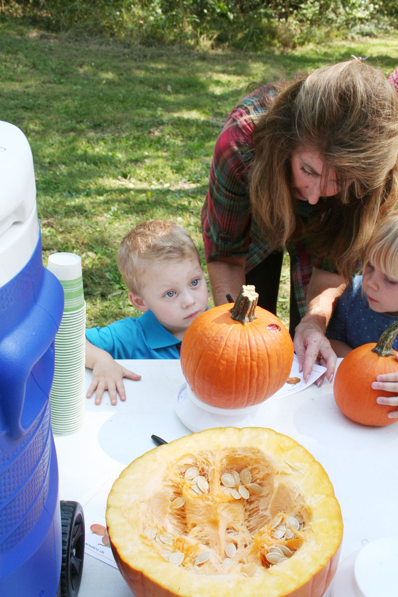 Dylan Thompson and Norah Peterson weigh their pumpkins and count its stripes. (Submitted Photo)