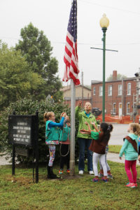 Local girl scouts raise the flag downtown in honor of A1C Cuddeback. (O'Fallon Weekly Photo by Nick Miller)