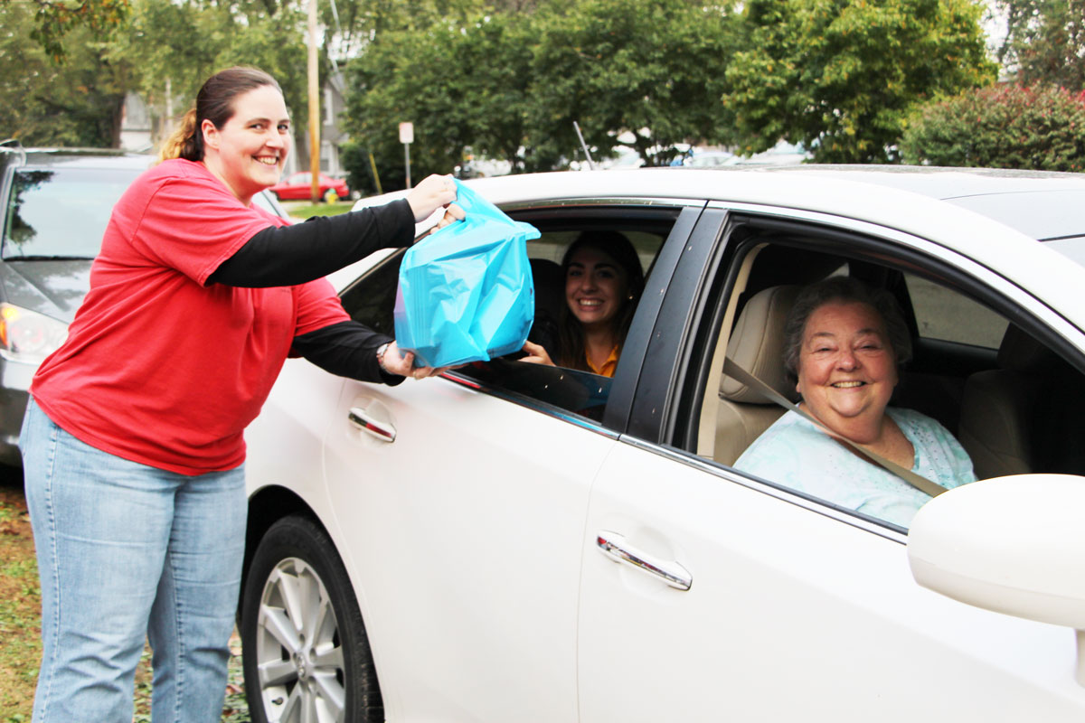 Tarrah Vaupel hands off some to-go meals in the drive-thru outside of the church.  (O'Fallon Weekly Photo by Nick Miller)
