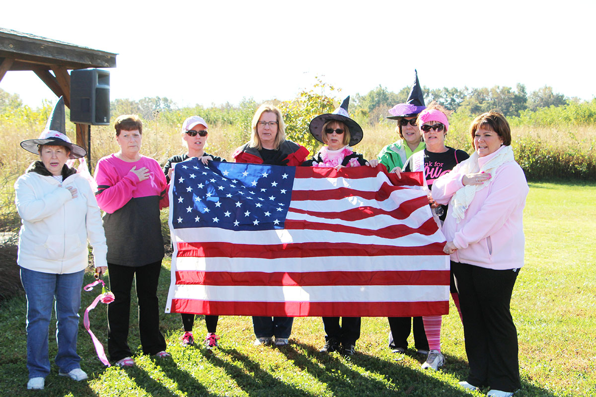 Pictured are the cancer survivors at the walk, leading those in attendance in the Pledge of Allegiance.  (O'Fallon Weekly Photo by Nick Miller)