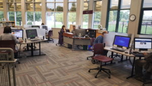 Patrons are busy on the Library's computers while Ryan Johnson, Adult Services Manager,  assists a patron at the Help Desk (Submitted Photo)