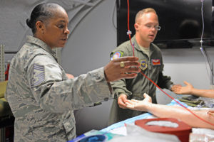 Air Mobility Command Command Chief Master Sgt. Shelina Frey learns about the 375th Aeromedical Evacuation Squadron's training platforms from Staff Sgt. Ryan Edwards, 375th AES. (U.S. Air Force photo/Senior Airman Erica Fowler)