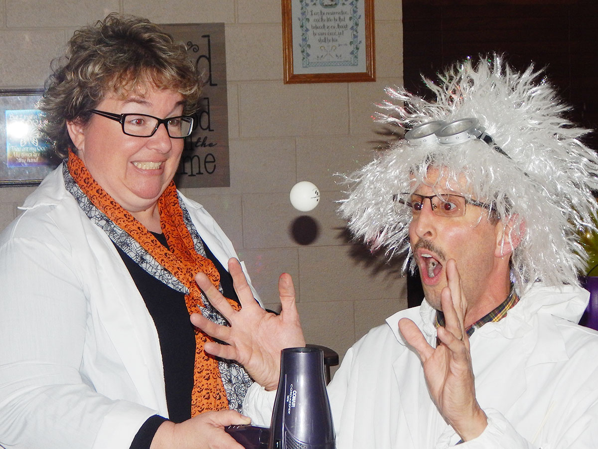 Pastor Don Long and his wife, Becky, posing as mad scientists to give children a fun, eccentric show as they hovered a ping pong ball in the air. (O'Fallon Weekly Photo by Kimberly Bennett)