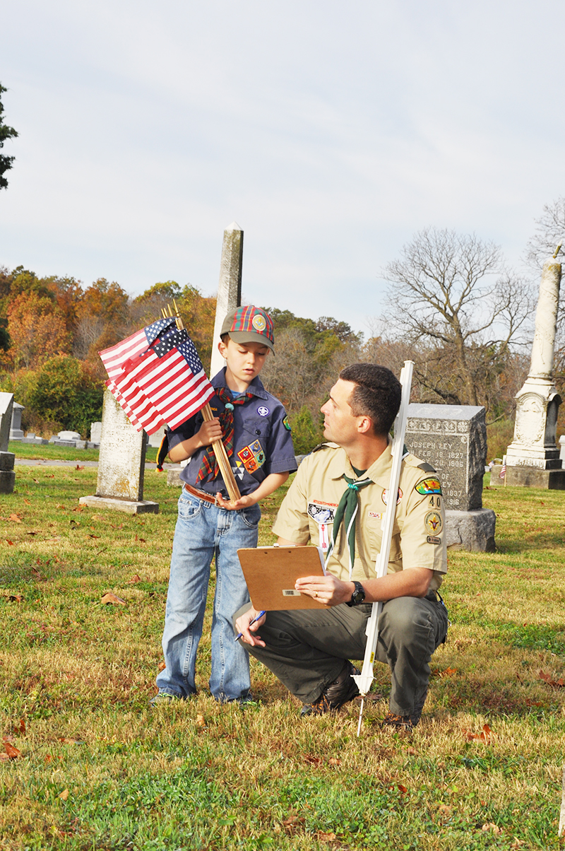 Cub Scout Pack 40 Member Evan Matthews assists his father, the assistant Scout Master for Troop 40, Stephen Matthews.