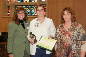 HSHS St. Elizabeth's Hospital CEO, Peg Sebastian (left), along with Regina Peterson, MSN, RN, Nurse Manager of Staff Development (right), award Sarah Krumeich, RN, of the Critical Care Unit with the National DAISY Award for Extraordinary Nurses. (Submitted Photo)