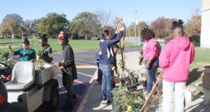 Independent Living and Life Skill teacher Jessica Day helps students figure out where plants, trellises and edgers should be placed around the Panther Dome. (O'Fallon Weekly Photo by Angela Simmons)