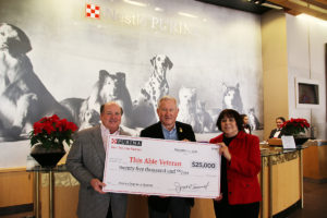 Nestle Purina President and CEO Joseph Sivewright (left) presents Phil Goodwin and President of This Able Veteran Pam Largent with a $25,000 donation. The gift will be used to pay for one dog to go through the  vetting process and service dog training to be placed with a veteran suffering from PTSD. (Submitted Photo)