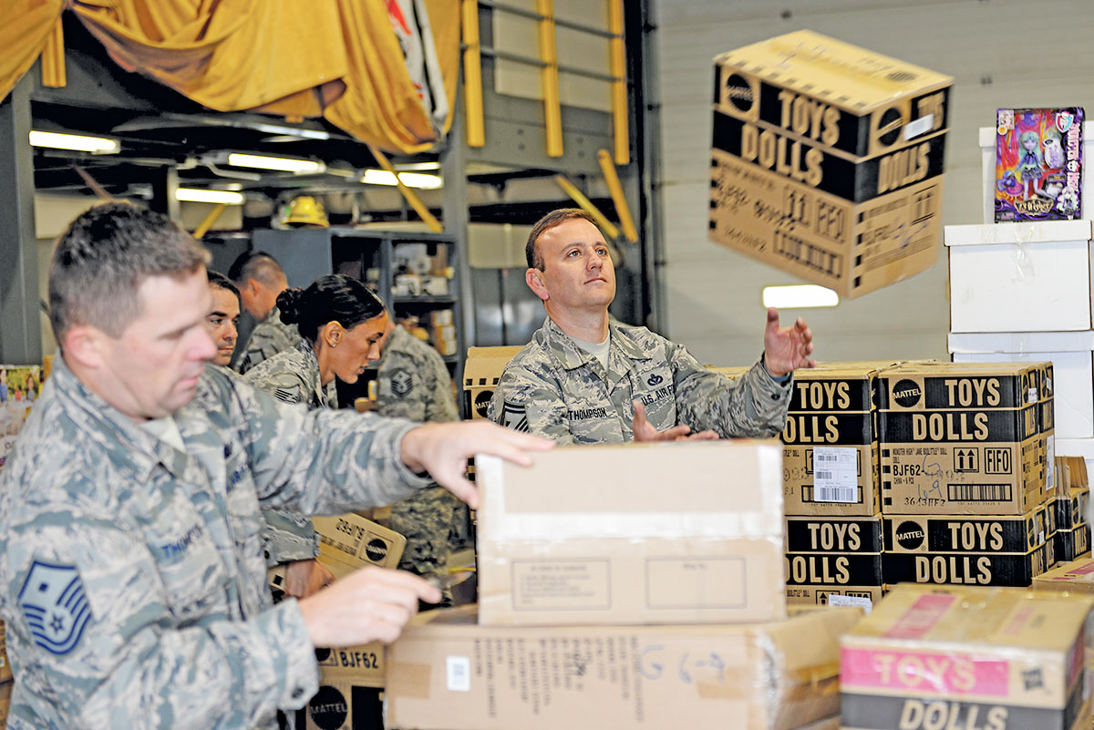 Senior Master Sgt. Stephen Thompson, the 835th Cyberspace Operations Squadron First Sergeant, catches a box of toy dolls at the Civil Engineering Squadron Compound (U.S. Air Force Photo by Senior Airman Megan Friedl)